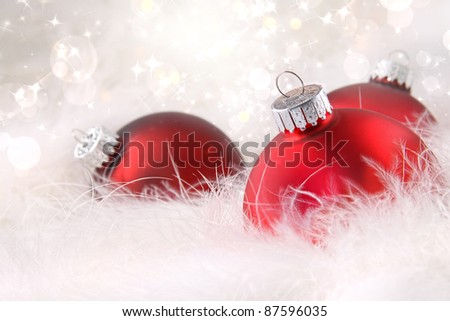 Red Christmas balls in soft white feathers - stock photo