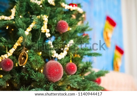 Red Christmas balls on a Christmas tree on a background of blue old doors in the New Year's room decorated. Garland of popcorn. Christmas tree in the living room with sofa. Fashionable winter interior