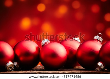 Red Christmas balls with a colorful party light bokeh background in orange to red tones with copy space for your seasonal greeting or advert #517471456