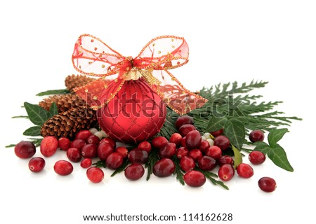 Red christmas bauble with bow, cranberry fruit, ivy, mistletoe, pine cones and cedar cypress leaf sprigs over white background.