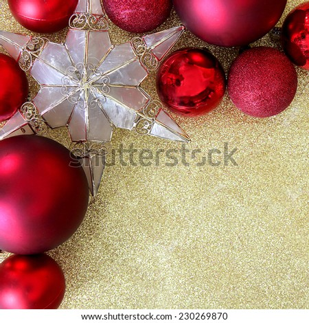 Red Christmas bulb decorations and a star shaped tree ornament border the corner of a background gold glitter fabric with copy-space.