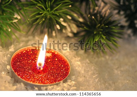 Red Christmas candle in snow with fir branch in the evening
