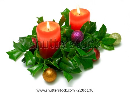 Red Christmas candles, with holly and baubles, isolated on white