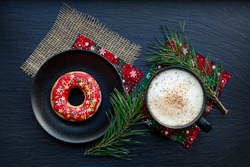 Red Christmas cookies and a Cup of coffee on a black dish