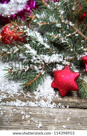 Red Christmas decoration on spruce branches with snow