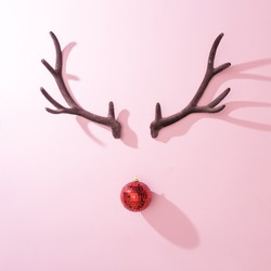 Red Christmas disco ball bauble with reindeer antlers on pink background. Minimal New year Santa concept. Flat lay.