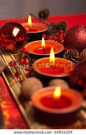Red Christmas festive candles with Christmas balls and walnuts