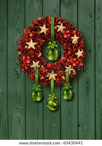 Red Christmas garland with green glass balls on old wooden door - stock photo