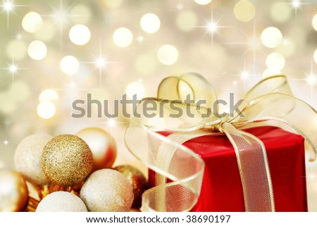Red Christmas gift box and baubles on background of defocused golden lights.