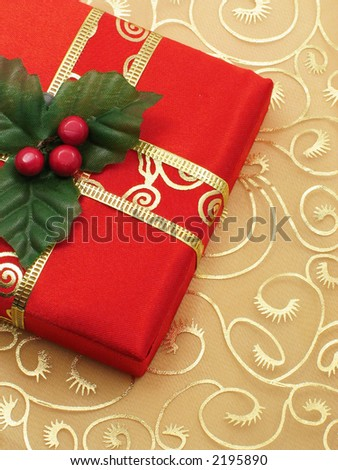 Red Christmas gift box with gold ribbon on gold silk background.