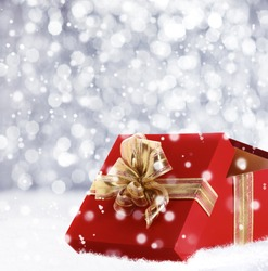 Red Christmas gift box with its lid propped at an angle in front to display the beautiful shiny metallic gold ribbon with falling winter snowflakes and copyspace for your greeting or wishes