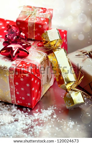 Red Christmas gift boxes and cracker on snowflakes and bokeh background