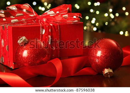 Red Christmas gift with ornaments in front of tree