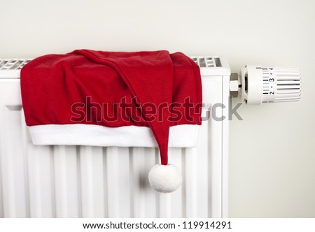 Red christmas hat placed on white home heating radiator with thermostat