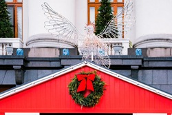 Red Christmas house decorated with green wreath and red ribbon with art installation of illuminated angel. Lamps. Lights. City. Outdoor. Market. Holidays. Celebration. Shop. Spruce