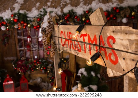 Red Christmas Label on Wooden Booth Wall with Lights and Christmas Ornaments Inside the House.
