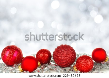Red Christmas ornament border with twinkling silver light background