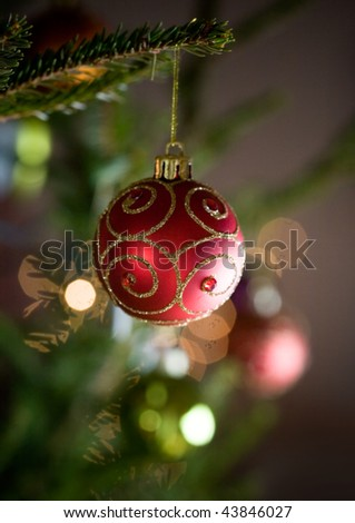 Red christmas ornament hanging from christmas tree