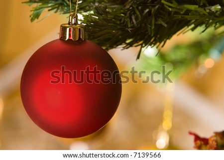 Red christmas ornament hanging in christmas tree, against light background