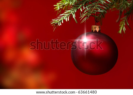 Red Christmas ornament hanging, with copy space to the left.