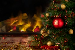 Red Christmas ornament with simbol of New Year on a Fir Tree.  Fireplace in bluried background. Christmas holidays background with copy space. Abstract blur. Soft focus. Minimalist black concept.