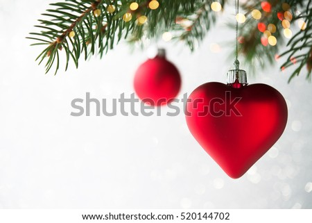 Red christmas ornaments, heart and ball, on the xmas tree on glitter bokeh background with twinkle lights. Merry christmas card. Winter holiday theme. Happy New Year. Space for text.  #520144702