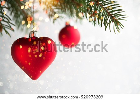 Red christmas ornaments, heart and ball, on the xmas tree on glitter bokeh background with twinkle lights. Merry christmas card. Winter holiday theme. Happy New Year. Space for text.