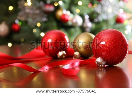 Red Christmas ornaments on a table with  decorated tree in  background.