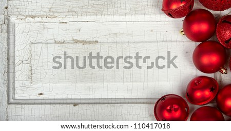 Red Christmas ornaments on antique cracked wood panel