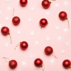 Red Christmas ornaments on pale pink background.