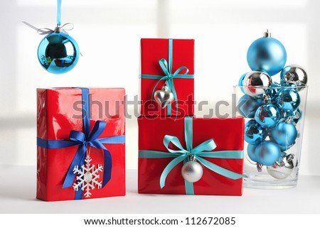 Red christmas present with blue ribbon and christmas spheres
