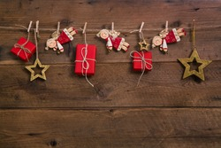 Red christmas presents with golden angels hanging on an old wooden wall.