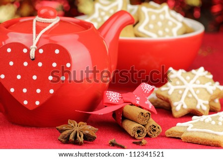Red Christmas table setting with teapot and gingerbread cookies
