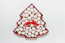 Red Christmas tree outline filled with white fluffy balls and red satin bow on white background.