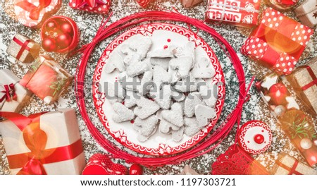 Red circle from decorative wands, with decorative Xmas plate and biscuits, cookies inside, on gray, stone, marble background, above view, greeting card #1197303721