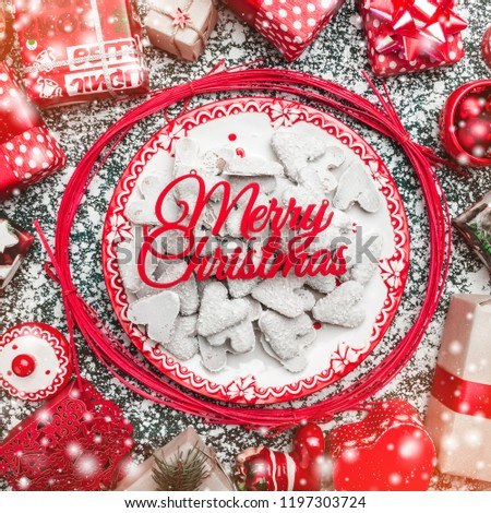 Red circle from decorative wands, with decorative Xmas plate and biscuits, cookies inside, snow effect, marble background, above view, greeting card #1197303724