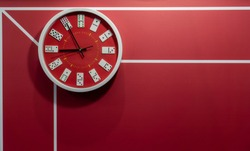 Red circle wall clock decorated with domino pieces hanging against red wall background.