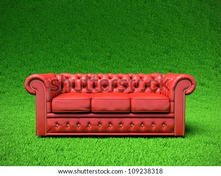 Red classic leather sofa on green field