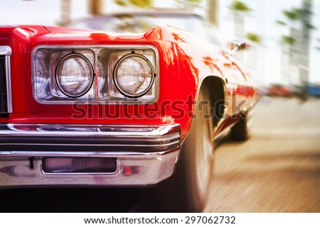 Red classic sports car driving fast, with motion blur background. Close up view.
