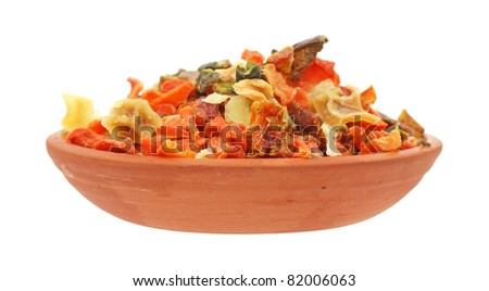 Red clay dish filled with dried vegetable seasoning on a white background.