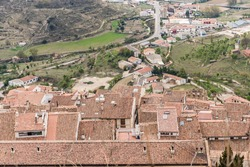 Red clay tile roofs in different heights and skylights and chimneys, with the driveway and surrounding fields, cultivation terraces with green grass and trees.