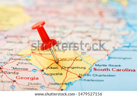 Red clerical needle on a map of USA, South South Carolina and the capital Columbia. Close up map of South South Carolina with red tack, United States map pin #1479527156