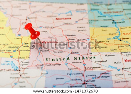 Red clerical needle on a map of USA, Wyoming and the capital Cheyenne. Close up map of wyoming with red tack, US map pin #1471372670