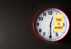 Red clock on dark gray copy space wall with note TIME IS MONEY, meaning time is precious for those who want to earn money, if invest it with compound interest ,wealth can grow over time
