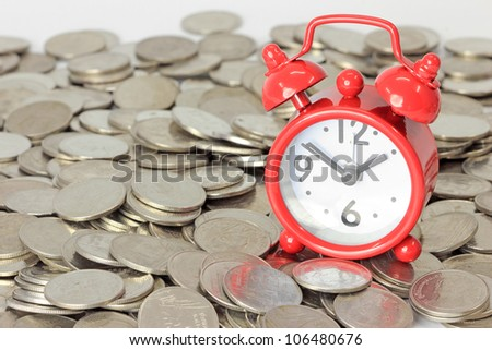 Red clock staying on coins. Time is money concept
