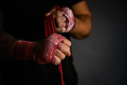 Red cloth hand wraps for muay thai fighting being wrapped around fist.