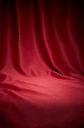 Red cloth waves texture background stage shot in table top for christmas background