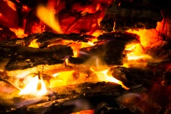 Red coals with fire on black background. Burning coals and wood in fire. Burning wood to keep warm and heat. Glowing embers in hot red and orange color