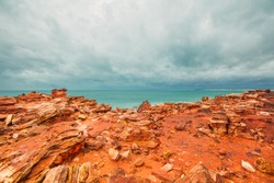 Red coastal cliffs at Gantheaume Point, Broome, Western Australia. a red-sandstone headland that juts out into the Indian Ocean from beautiful Cable Beach, Broome.