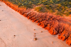 Red coastal cliffs of Riddell Beach in Broome, Western Australia at sunset